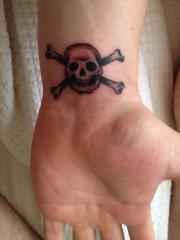 Skull and crossbones wrist tattoo